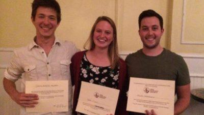 three students holding awards